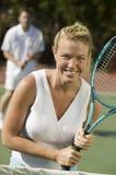 站立在网球净等待的服务画象的妇女 免版税库存照片