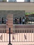 站立在美国垂直构成前面总领事馆的一个队列的人们  库存图片