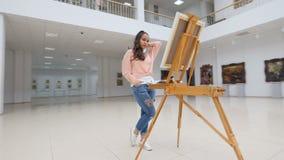 站立在美术画廊的空白的帆布前面的女孩 影视素材