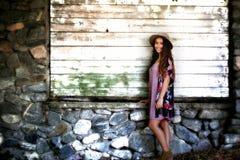 站立在老岩石和木头墙壁附近的逗人喜爱的女孩 免版税库存照片