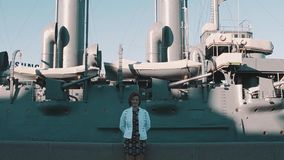 站立在老战舰博物馆前面的夏天礼服的俏丽的女孩 影视素材