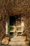 站立在老房子f游廊的两把柳条葡萄酒椅子  库存照片