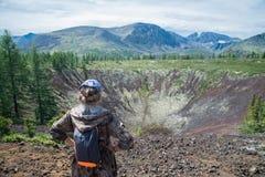 站立在老火山火山口顶部的小姐远足者享受美好的夏天风景看法  搭车妇女的高速公路 免版税库存图片