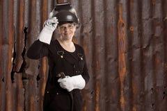 站立在老生锈的金属墙壁前面的女性焊工 库存图片