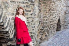 站立在老砖墙的可爱的妇女 免版税图库摄影