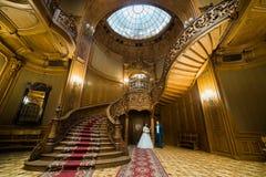 站立在老葡萄酒房子和宫殿的典雅的婚礼夫妇有大木台阶的 免版税库存照片