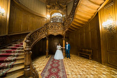 站立在老葡萄酒房子和宫殿的典雅的婚礼夫妇有大木台阶的 库存图片