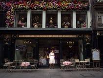 站立在老街道上的古色古香的波尔图商店前面的夫人 免版税图库摄影