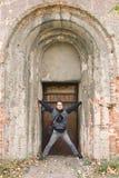 站立在老被成拱形的门的人 库存照片
