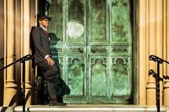 站立在老门前面的衣服的人 库存照片