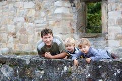 年轻站立在老Ge后墙壁的人和他的两个小男孩  图库摄影