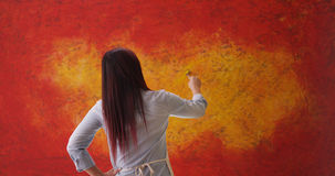 站立在背景前面的中国妇女艺术家 免版税库存图片