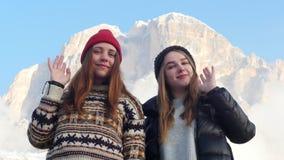 站立在背景山和挥动用他们的手的两年轻女人 股票视频