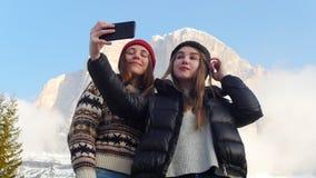 站立在背景山和采取selfie的两名年轻微笑的妇女 影视素材
