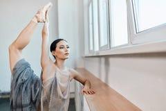 站立在脚趾的一条腿在pointe和举另一个高的芭蕾舞女演员 免版税图库摄影