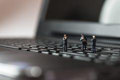 站立在膝上型计算机键盘的微型商人 免版税库存照片