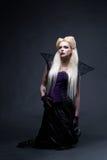站立在膝盖的美丽的白肤金发的女孩吸血鬼 免版税库存图片