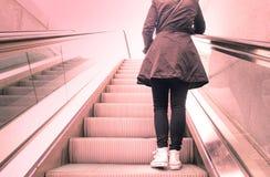站立在自动扶梯楼梯的女孩 免版税图库摄影