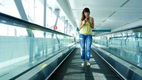 站立在自动走道,在地铁横穿的台阶的妇女,使用她的电话,通信方式,时兴 影视素材