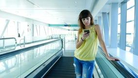 站立在自动走道,在地铁横穿的台阶的妇女,使用她的电话,通信方式,时兴 股票录像