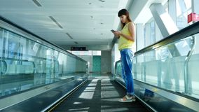 站立在自动走道,在地铁横穿的台阶的妇女,使用她的电话,通信方式,时兴 股票视频
