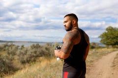 站立在自然本底的一个坚韧肌肉人 放松在做以后的爱好健美者炫耀锻炼户外 免版税库存图片