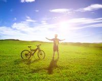 站立在自行车旁边的背包徒步旅行者有日出背景 免版税库存图片