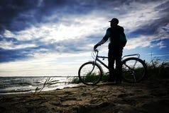站立在自行车旁边的年轻人骑自行车者 库存图片