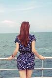 站立在船坞的女孩观看海海洋 库存照片