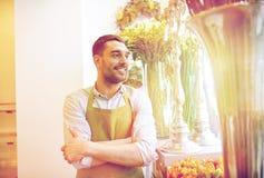 站立在花店的愉快的微笑的卖花人人 免版税库存图片