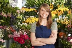 站立在花显示前面的商店的卖花人 免版税图库摄影