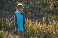 站立在草中的女孩 库存图片