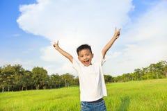 站立在草甸和培养手上的愉快的孩子 免版税图库摄影