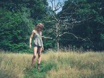 站立在草甸的少妇 免版税库存图片