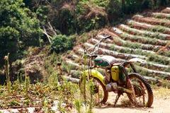 站立在草甸的摩托车旅客 免版税库存图片