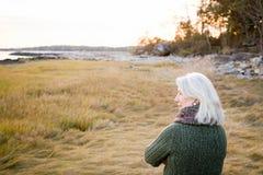 站立在草的妇女在海岸附近 免版税库存图片