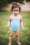站立在草的游泳衣的婴孩 免版税库存图片