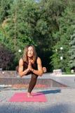 站立在草的瑜伽姿势的愉快的妇女在公园 图库摄影