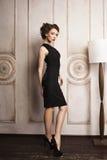 站立在落地灯附近的黑礼服的美丽的端庄的妇女 库存照片