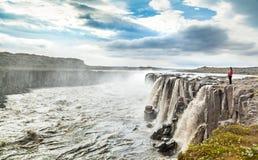 站立在著名Selfoss瀑布附近的妇女在Vatnajokull国家公园,东北冰岛 免版税库存图片