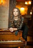 站立在葡萄酒钢琴附近的典雅的黑礼服的年轻美丽的深色的妇女 有长的黑发的肉欲的浪漫夫人 免版税图库摄影