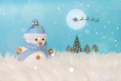 站立在蓝色冬天圣诞节雪背景中的愉快的雪人 圣诞快乐和新年好贺卡与拷贝空间 免版税库存照片