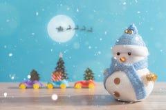 站立在蓝色冬天圣诞节雪背景中的愉快的雪人 圣诞快乐和新年好贺卡与拷贝空间 免版税库存图片