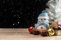 站立在蓝色冬天圣诞节雪背景中的愉快的雪人 免版税库存图片