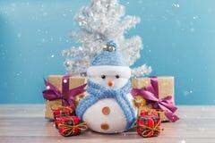 站立在蓝色冬天圣诞节雪背景中的愉快的雪人 库存图片