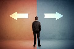 站立在蓝色和红色backgro的两个箭头前面的推销员 免版税图库摄影