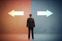 站立在蓝色和红色backgro的两个箭头前面的推销员 库存图片