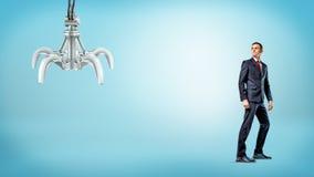 站立在蓝色背景的商人半转动看一只金属机器人手 免版税库存图片