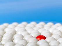 站立在蓝色背景的白色球围拢的红色球 库存照片