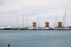 站立在蓝色陆间海附近的三台老风车 免版税库存照片